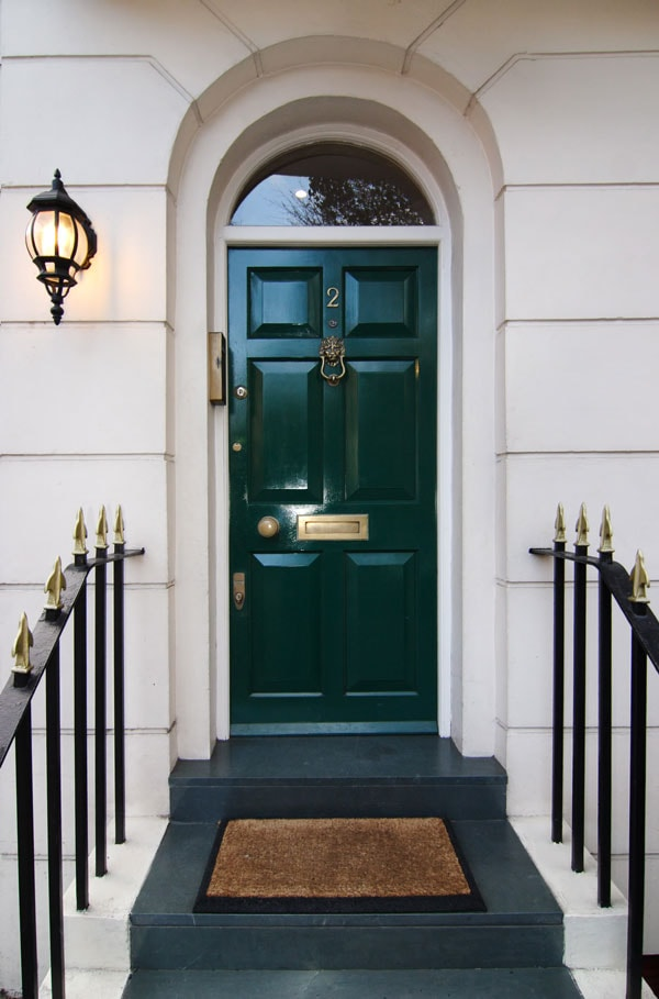 glossy green front door with limestone exterior