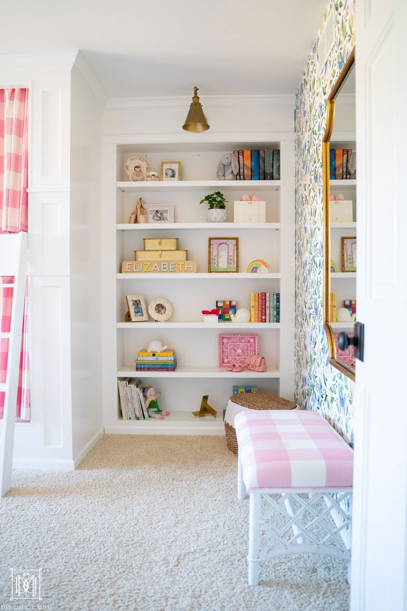 white built-in bookcases in girls bedroom with brass sconce and pink buffalo check design elements next to a green and white wallpapered wall