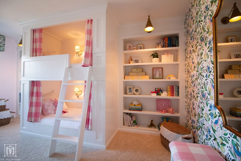 built-in bunk beds in girls bedroom with lights on and bookcase--beautiful shared girls pink and white and green bedroom