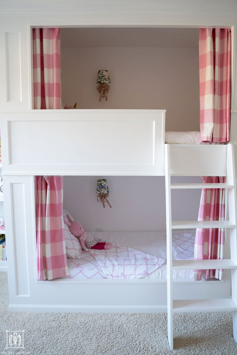 girls bunk room with built-in bunk beds and pink and white curtains made out of buffalo-check fabric
