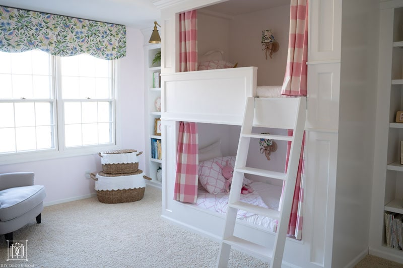 girls built-in bunk beds with traditional panelling and pink and white curtains in shared girls bunk room