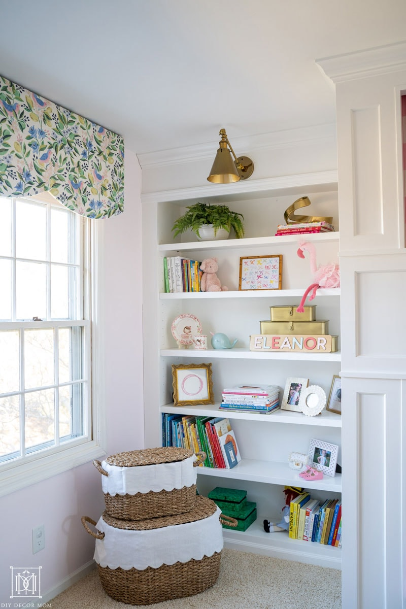 built-in bookcase in girls bedroom with fabric covered window valance and pelmet box