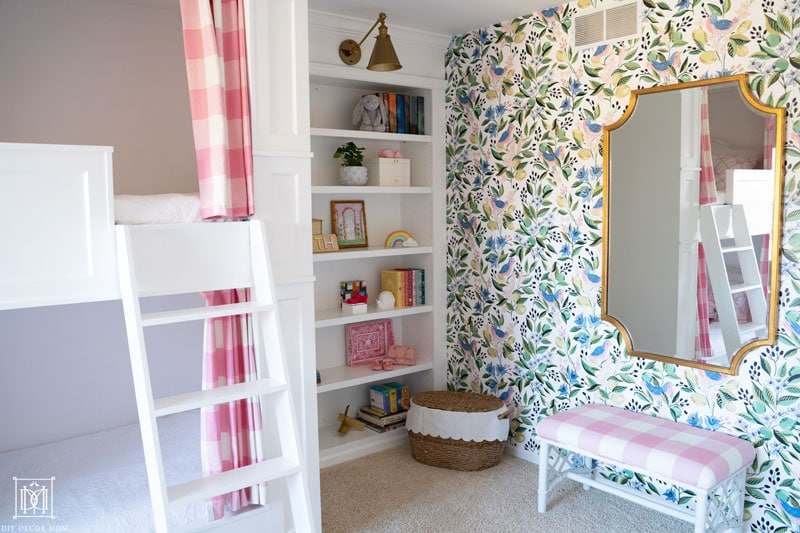 diy built-in bunk beds with curtains and white ladder in front of girls bedroom accent wall with wallpaper and gold and brass mirror and sconce