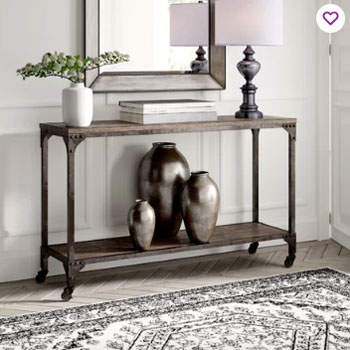 industrial console in entry with white walls and white trim and herringbone gray floors