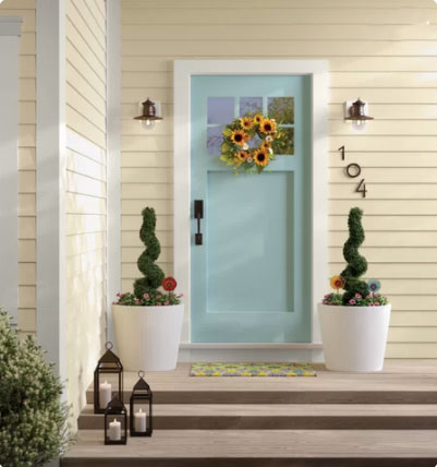 light green aqua front door with planters on either side and lanterns