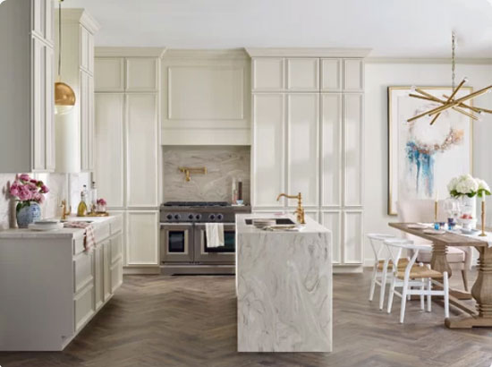 off white kitchen cabinets with waterfall countertop and herringbone floors