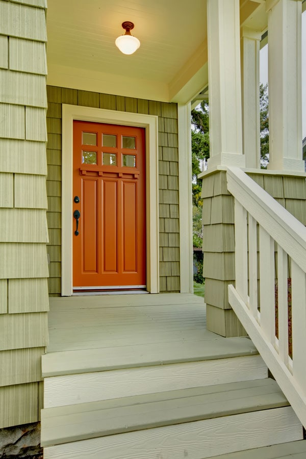orange front door and green exterior shingles on craftsman house