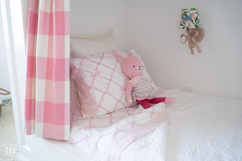 girls bed in shared girls bunk room with fabric covered lampshade and pink and white bedding