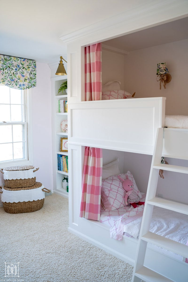 bunk beds with curtains in pink and white buffalo check and a white ladder in girls bunk room shared bedroom