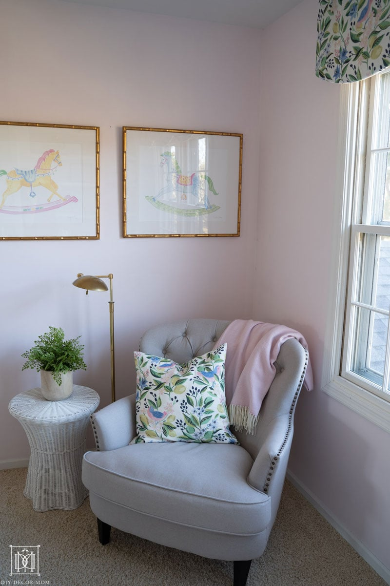 pale pink walls in shared girls bedroom with bunk beds- photo of a chair with a brass reading light and a white scalloped wicker side table with a green plant on top