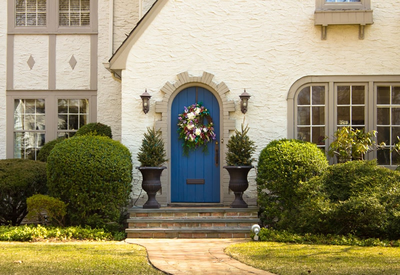 teal arched front door on tan stucco exterior