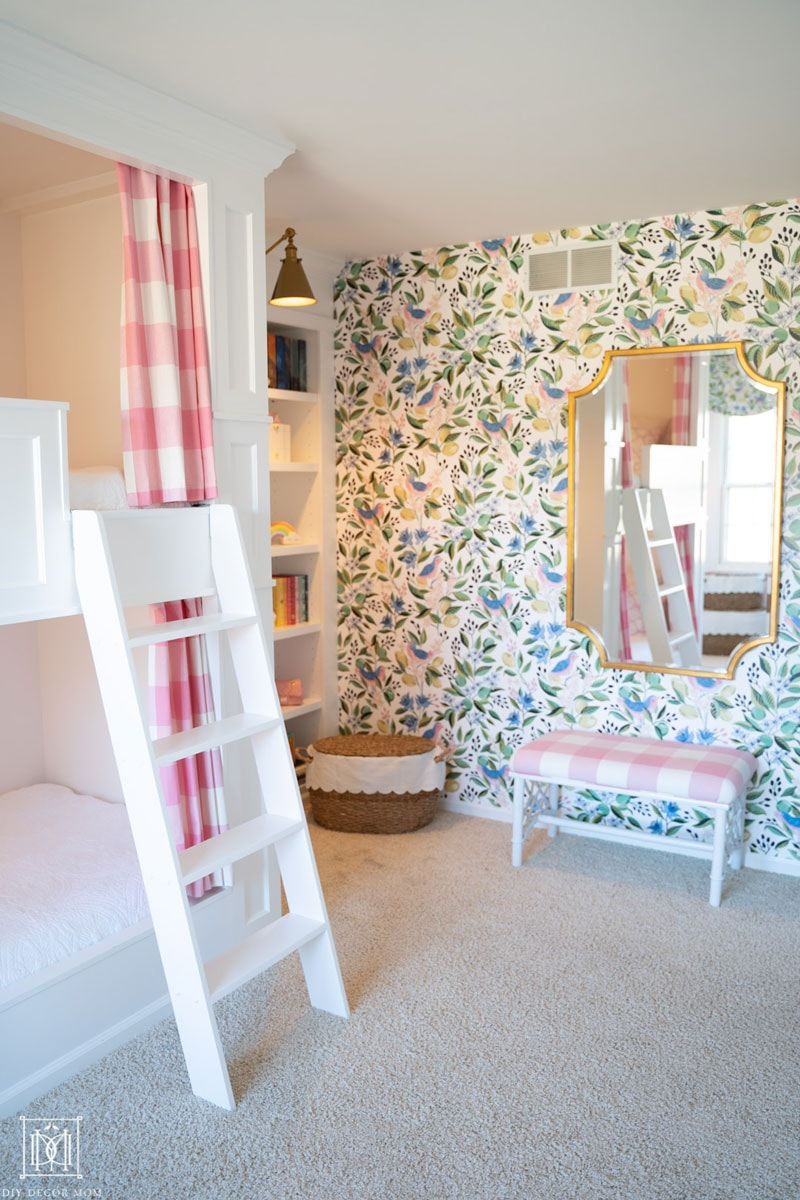 Built-in bunk beds with curtains and ladder in girls bedroom with preppy chinoiserie green and white wallpaper and beautiful gold mirror over a chinoiserie style bench covered in pink and white buffalo check.