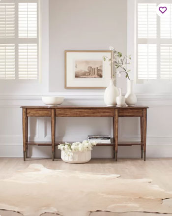 wood table and console in formal room with white trim and wainscoting