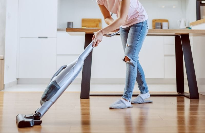 woman using a steam mop on hardwood floors
