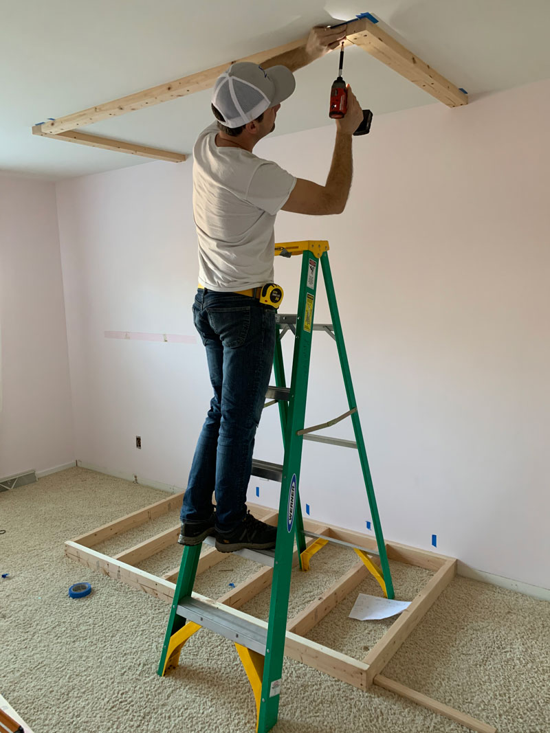 man attaching cleats to the ceiling for diy bunk bed