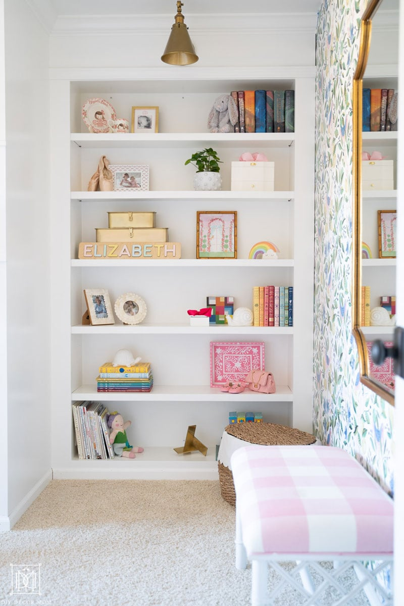 white built-in bookshelves in bedroom with gold sconce