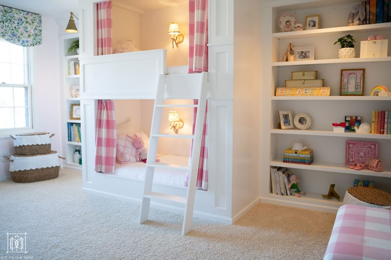 beautiful white built-in bookcases with bunk bed in girls bedroom
