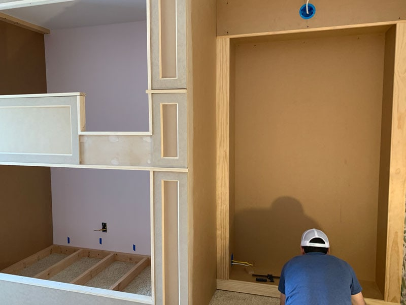 man installing the trim and framing in a built in bookcase