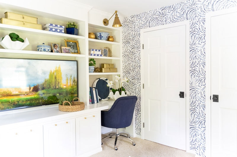 built-in desk with grasscloth bookshelves and blue and white wallpaper on walls