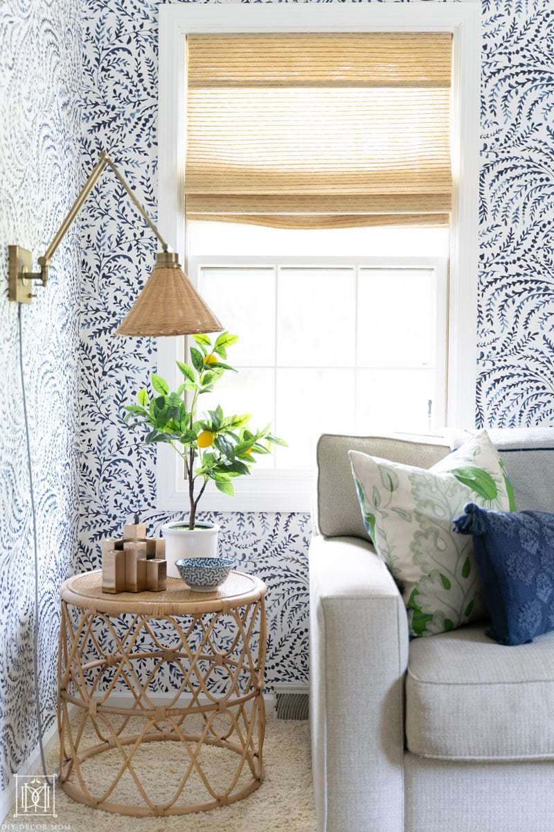 bamboo shades with bamboo table and wicker lamp shade in blue and white wallpapered office/ den