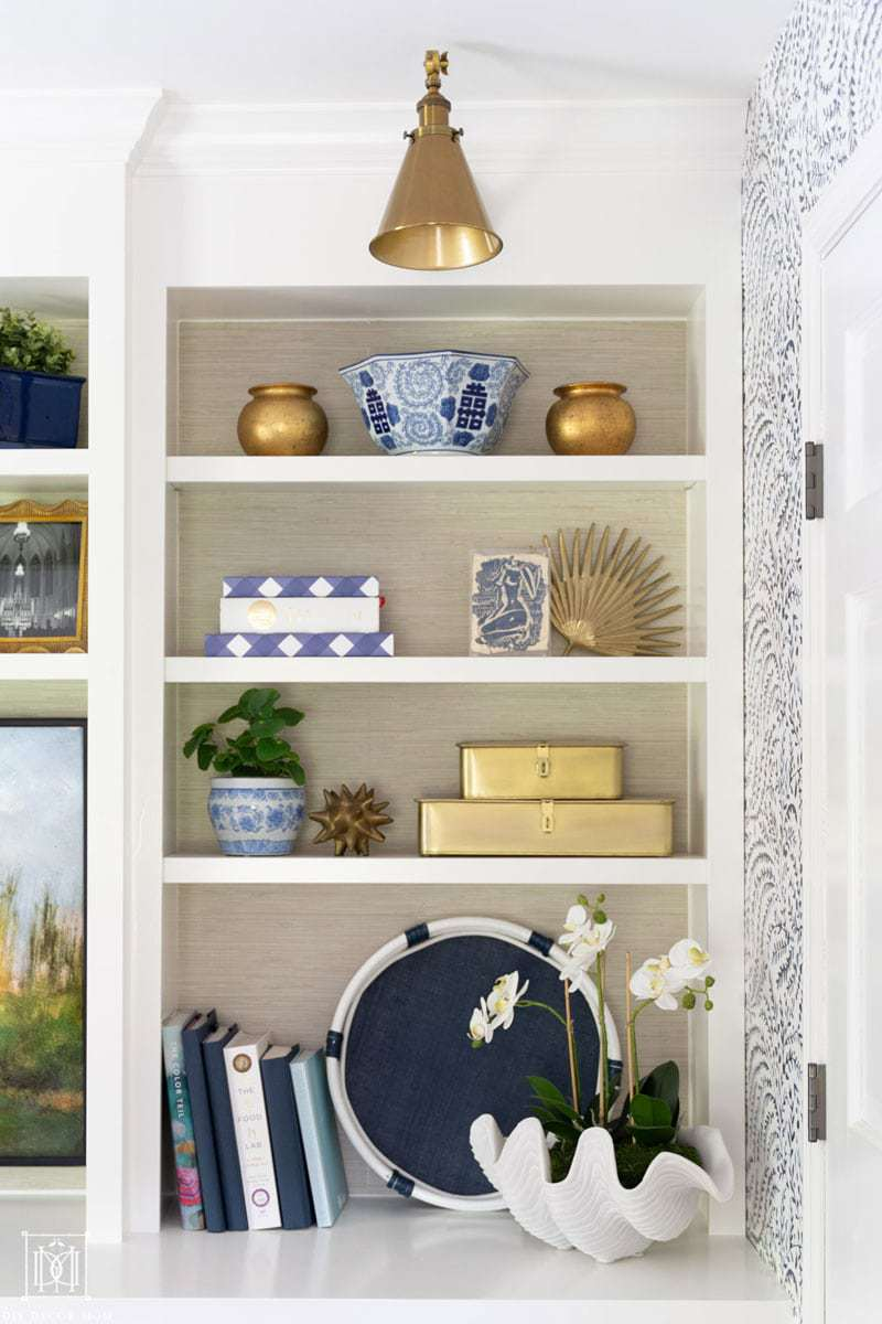 styled bookshelves with faux grasscloth wallpaper