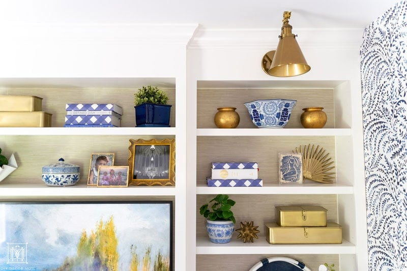 styled built-in bookshelves with faux grasscloth wallpaper backs