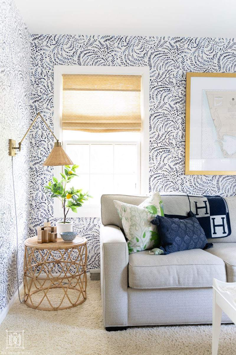 nautical coastal office reveal with bamboo blinds, rattan side table, wicker sconces, and blue and white wallpaper