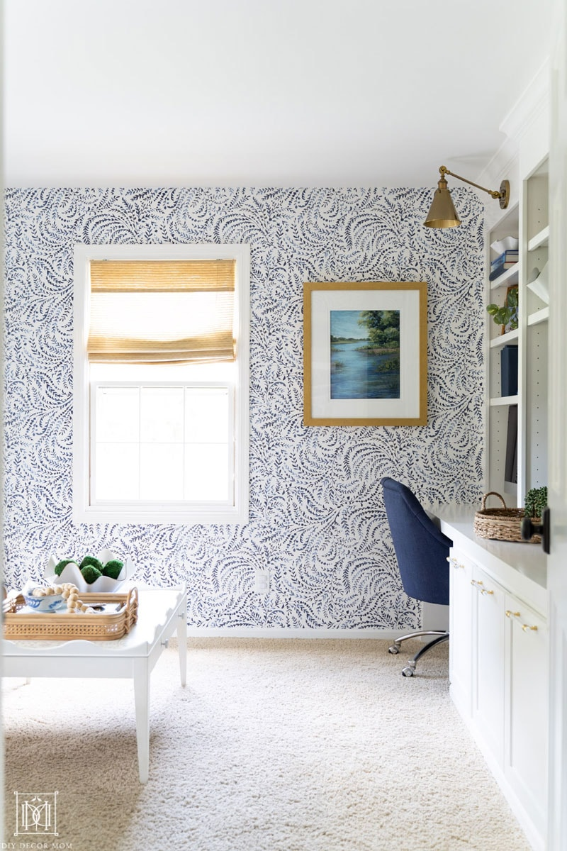 blue and white wallpapered office with built-in desk and bookshelves