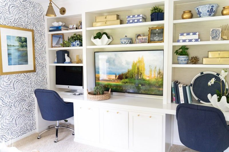 white diy built-in bookshelves and desk with grasscloth wallpaper and brass sconces with two work stations and TV in the middle