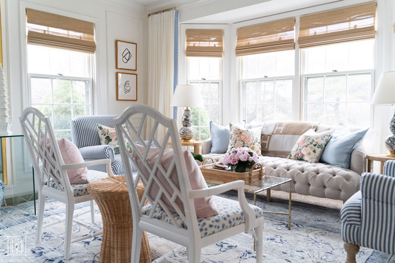 chippendale chairs in grandmillennial living room with blue oriental rug and chintz pillows and bamboo blinds
