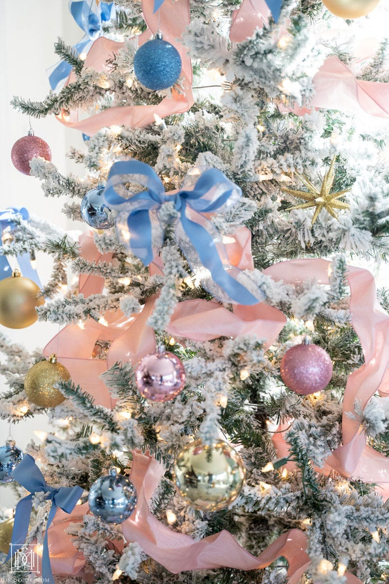 pink and blue ribbons and ornaments on flocked christmas tree