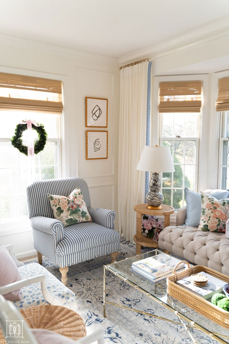 paneled white living room with acrylic curtain rods and bamboo blinds