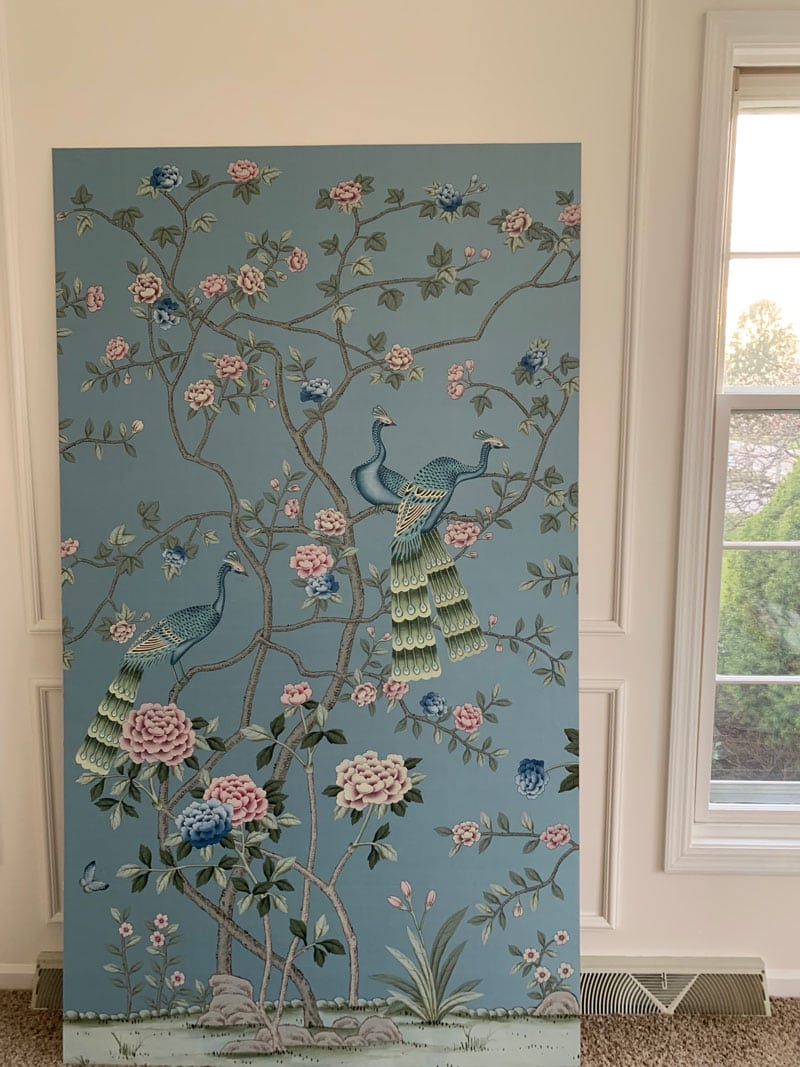 mounted but not hung chinoiserie panel leaning against wall in white wall living room
